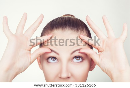 Portrait of a young woman with wrinkles on his forehead on white background - stock photo
