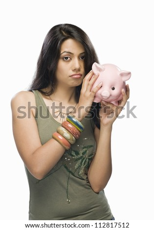 Portrait of a young woman worried with a piggy bank - stock photo