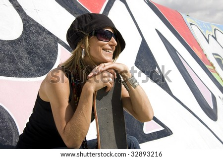 Portrait of a young women with a graffiti wall on background - stock photo