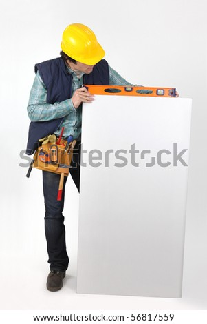 Portrait of a young worker with a white panel for message - stock photo