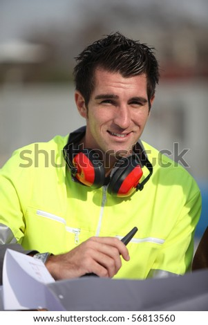 Portrait of a young worker with walkie-talkie and noise-canceling headphones - stock photo