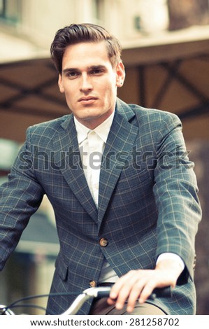 Portrait of a young young handsome businessman riding bicycle  - stock photo