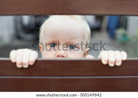 Portrait of abandoned by parents baby boy with staring blue eyes, sad and lonely face expression, looking out through fence. Social problems, family abuse, children stress and negative emotions - stock photo