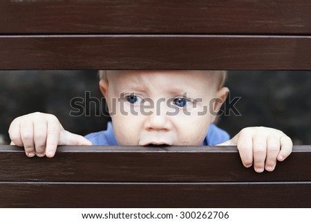 Portrait of abandoned by parents little baby boy with staring blue eyes, sad and lonely face expression, looking out through the fence. Social family problems and children stress and negative emotions - stock photo