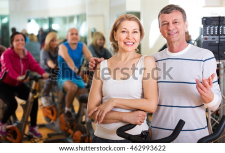 Portrait of active happy elderly couple exercising in gym