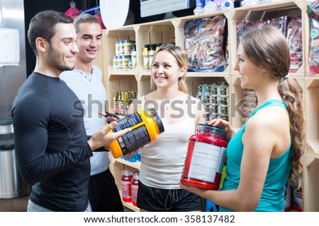 Portrait of active people with sport nutrition products in shop  - stock photo
