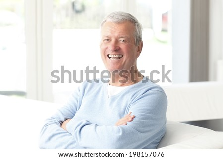 Portrait of active senior businessman sitting at sofa.  Small business. - stock photo