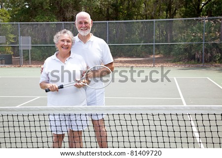 Portrait of active senior couple together on the tennis court. - stock photo
