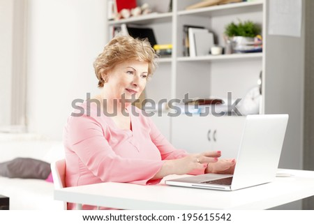 Portrait of active senior woman surfing on internet. - stock photo