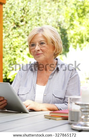 Portrait of active senior woman using digital tablet while sitting at nursing home garden.
