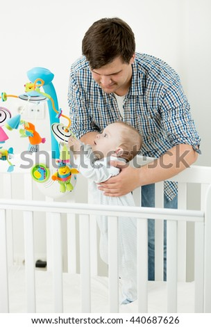 Portrait of adorable baby boy playing in cot with his father - stock photo