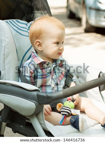 Portrait of adorable baby boy sitting in stroller - stock photo