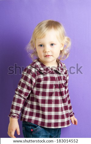 Portrait of adorable baby girl in checkered shirt isolated on purple background - stock photo