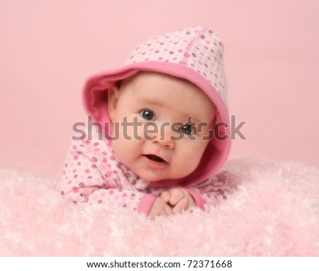 Portrait of adorable baby girl on pink blanket and background, lying on tummy