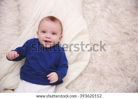 Portrait of adorable baby in blue pullover on the floor, close up - stock photo