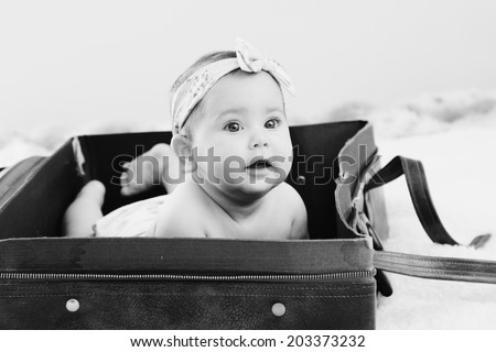 Portrait of adorable baby lying in vintage bag - stock photo