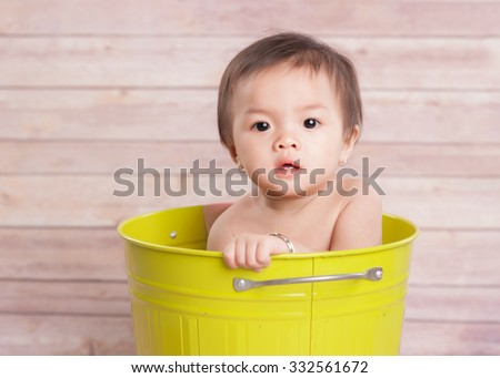 Portrait of adorable baby sitting and looking at the camera - stock photo