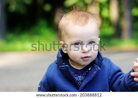 Portrait of adorable blond baby boy with blue eyes in the blue coat doing his first steps and holding his mother finger - stock photo