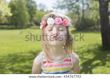 portrait of adorable blond young girl in preschool age sending air kiss and wearing flowers in hairs, bright striped dress on green grass lawn outdoors  - stock photo