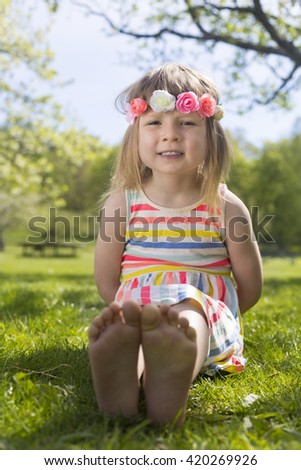 portrait of adorable blond young girl in preschool age wearing flowers in hairs outdoors on traditional swedish midsummer celebration - stock photo
