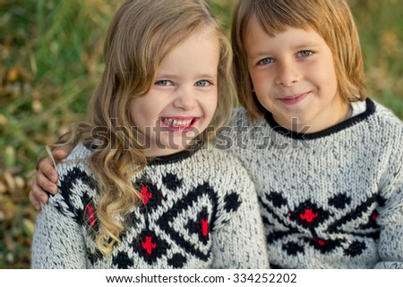 Portrait of adorable brother and sister smile and laugh together while sitting outdoors. happy lifestyle kids  - stock photo