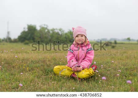 portrait of adorable cheerful  little girl sitting in rural field with dried grass and small flowers and holding a flower in hands, looking happy - stock photo