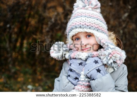 Portrait of adorable girl in grey hat, scarf and coat  outdoor in winter park - stock photo