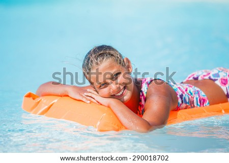 Portrait of Adorable girl relaxing at swimming pool - stock photo