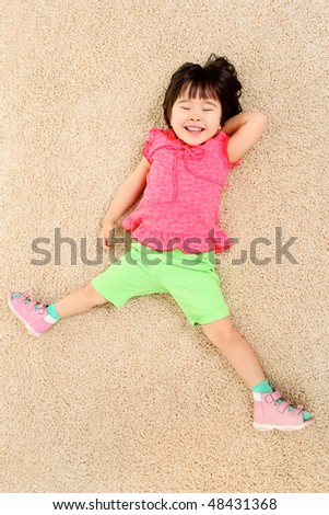 Portrait of adorable girl relaxing on the floor - stock photo