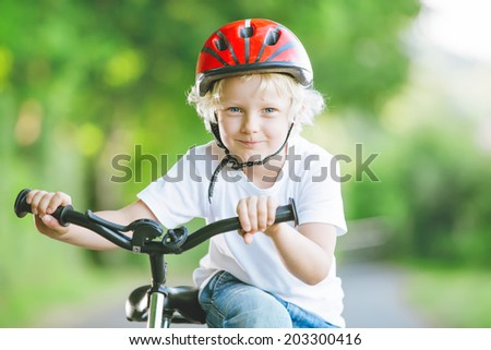 Portrait of adorable handsome little boy, happy smiling scholar with bike and helmet, in the park, at summer. Concept of childrens sport and healthy style of life. - stock photo