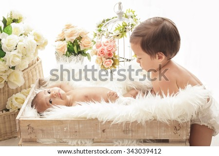 portrait of adorable handsome toddler playing with his little sister - stock photo