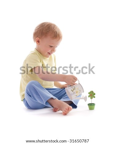 Portrait of adorable happy boy using watering-pot want to water artificial wooden flower - stock photo