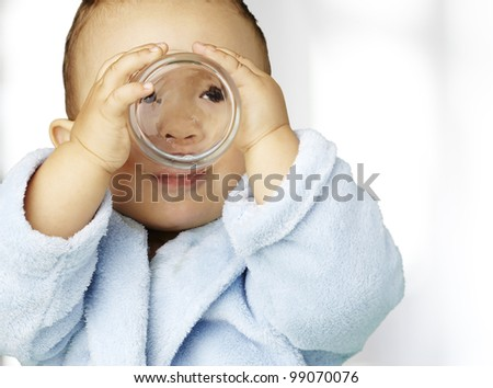 portrait of adorable infant with blue bathrobe drinking water in - stock photo