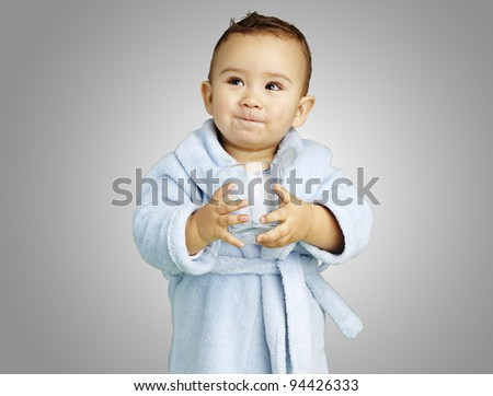 portrait of adorable infant with blue bathrobe holding a glass over a grey background - stock photo