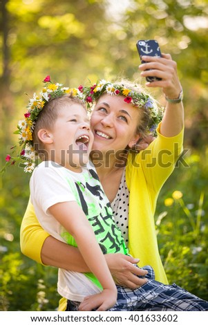 Portrait of adorable kid boy with his young mother taking selfie in the sunny park. Happy family in flower wreaths making photo with smartphone and smiling outdoors on a summer day. - stock photo
