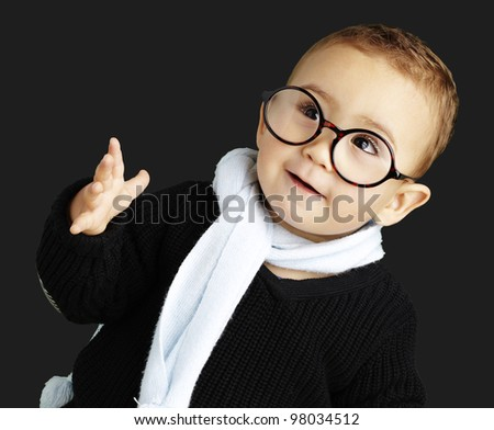 portrait of adorable kid gesturing doubt against a black background - stock photo