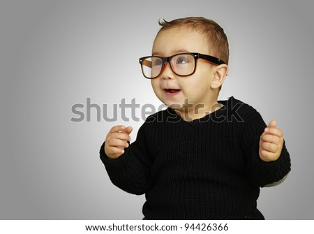 portrait of adorable kid wearing glasses and gesturing over grey background - stock photo