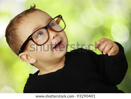 portrait of adorable kid wearing vintage glasses against a nature background - stock photo