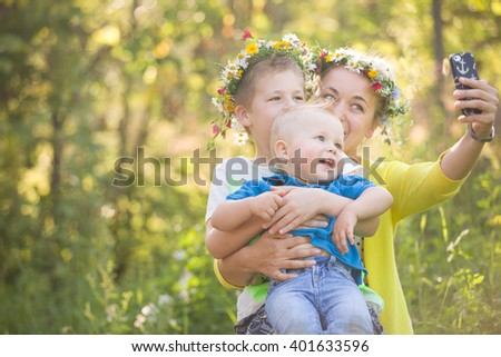 Portrait of adorable kids with their young mother taking selfie in the sunny park. Happy family in flower wreaths making photo with smartphone outdoors on a summer day. Boys and mom smiling. - stock photo
