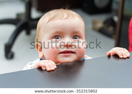 Portrait Of Adorable Little Boy Smiling Behind Table - stock photo