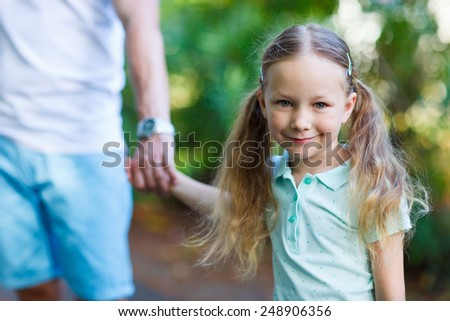 Portrait of adorable little girl outdoors on summer day holding her father hand - stock photo