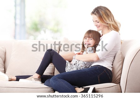 Portrait of adorable little girl sitting at home with her mother and having fun. - stock photo