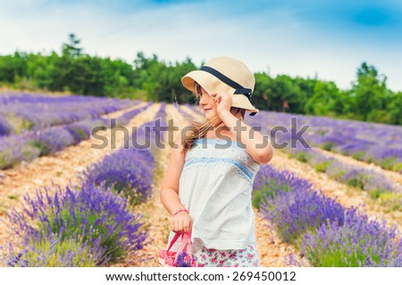 Portrait of adorable little girl wearing a hat, playing in lavender field, Provence, France - stock photo
