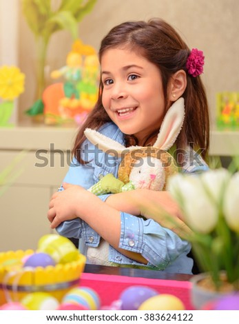 Portrait of adorable little girl with pleasure hugging her friend, soft toy Easter bunny, having fun at home in happy holiday day