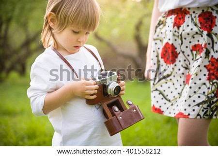 Portrait of adorable little kid boy sitting on an old tree and looking into distance in a sunny summer day. Blond child walking in the park. Sunset. Outdoors. - stock photo