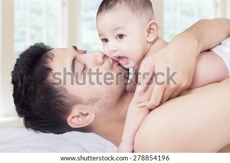 Portrait of adorable male baby with his father on the bedroom