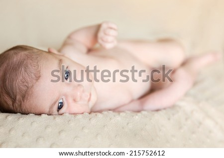 Portrait of adorable newborn baby boy with open eyes lying down over a blanket