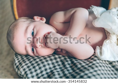 Portrait of adorable newborn baby resting lying over a plaid blanket on top of a vintage travel suitcase - stock photo