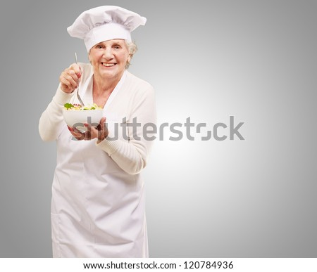 portrait of adorable senior cook woman eating salad against a grey background - stock photo