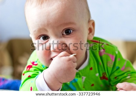 Portrait of adorable serious baby boy eating cabbage and looking at camera - stock photo